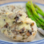 Gouda and mushroom stuffed chicken with wild rice and asparagus on pottery plate.