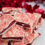 Vertical image for red velvet bark. Close-up of bark piled on white plate with red tinsel in background